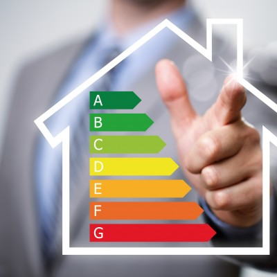 Businessman pointing to energy efficiency rating chart and house icon concept for performance, efficiency and environmental conservation
